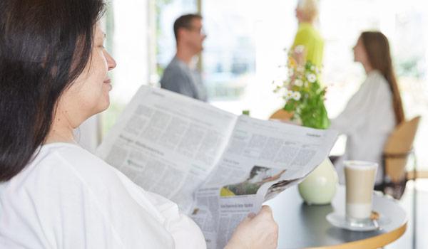 Zeitunglesen im Café